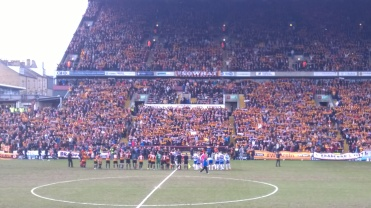 The teams line up in front of a sea of Claret and Amber.